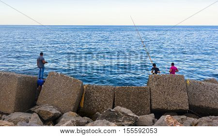 amateur fishermen who fish from the dock in a port