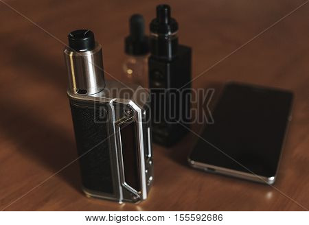 Vape devices, mods, dripping atomizer, tank, E-cigarette for vaping, liquid in the bottle and mobile phone on wooden table
