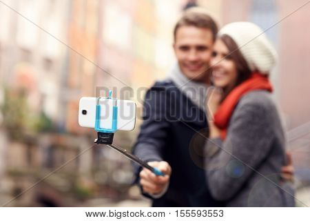 Picture showing young couple taking pictures with sefie stick