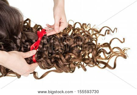 Female hands bind ribbon beam curly hair isolated on white background.