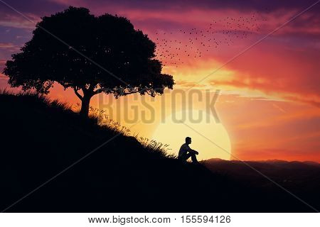 Boy sit alone on a hill in the center of nature over a sunset background. Standing away from the crowd waiting for the healing power of the nature.