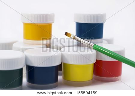 jars with gouache on white background and a rainbow gouache