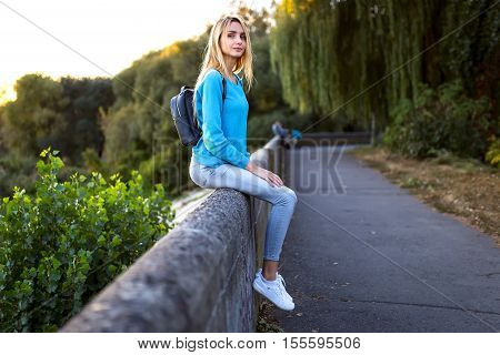Young stylish blonde girl with a black backpack in a turquoise jacket in white shoes and jeans sitting on the parapet and looking