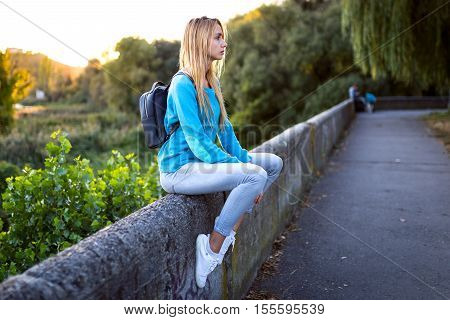 Young stylish blonde girl with a black backpack in a turquoise jacket in white shoes and jeans sitting on the parapet and think