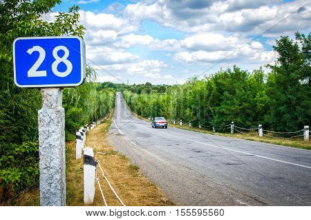 summer beautiful highway with clouds on the roadside stands a blue sign 28