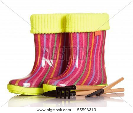 Children rubber boots with fabric inset, shovel and rake isolated on white background.