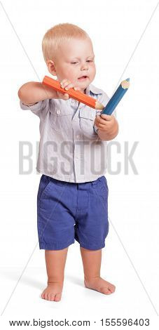 Charming boy in a shirt and shorts standing and holding two large pencil isolated on white background.