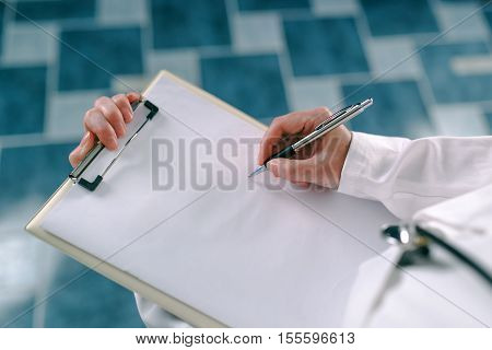 Female doctor in white uniform writing on clipboard paper patient's medical history. Woman as health specialist in exam er disease prevention visit check or healthcare lifestyle concept poster
