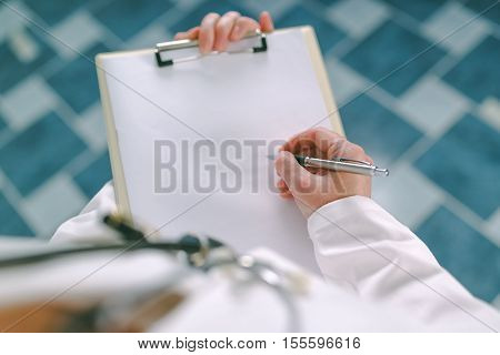 Female doctor in white uniform writing on clipboard paper as copy space for patient's medical history or medicine prescription. Woman as health specialist in exam er disease prevention visit check or healthcare lifestyle concept poster