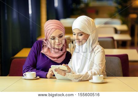Two Muslim women in a cafe shop online using electronic tablet Ufa