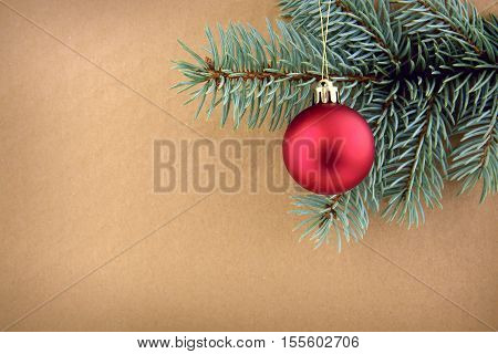 Red Christmas ball on green spruce branch isolated on brown background. Christmas background.