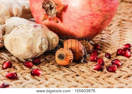 ginger pomegranate rosehip on a straw table. fruit from colds and anemia