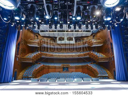 View from the illuminated empty concert stage to the lit empty auditorium in a large concert hall in the city Penza. Russia Penza region April 2014