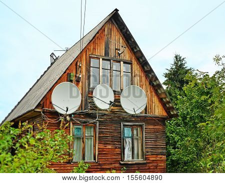 Several different antennas on a wall of the shabby old wooden house in rural areas as a metaphor of technical progress