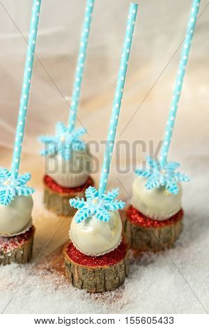 Lollypops side view on the snow. Decorated with sugar snowflakes. Close-up.