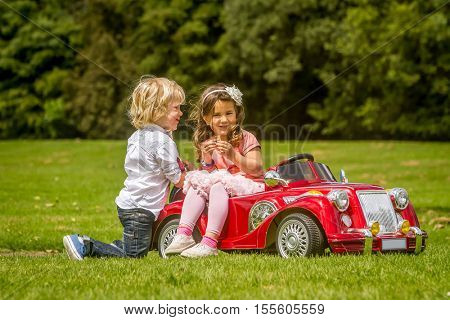 young happy children - boy and girl - driving a toy car outdoors in park