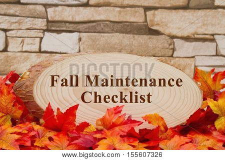 Fall maintenance checklist message Some fall leaves a pumpkin and wood plaque on weathered brick with text Fall Maintenance Checklist