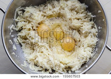 Grated potato and three eggs with seasoning for latkes in metal bowl from above