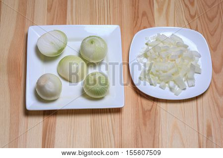 cut and whole onions lie on a white plate on a wooden table. Small cut onions lie on a white plate on a wooden table.