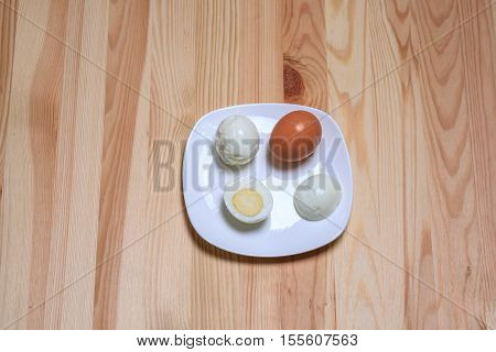 Boiled eggs lie on a white plate on a wooden table. Egg in a shell, without shell and one egg is cut in half.