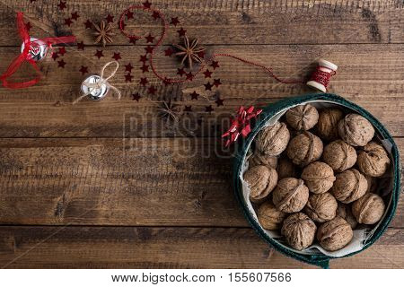 Walnuts in Decorative Tin and Festive Christmas Decorations on Rustic Wood Table