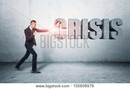 Businessman standing on the ground hitting a big 3D letter 'C' of a word 'CRISIS' with a fist. Business and management. Defeating crisis. Solving problems.