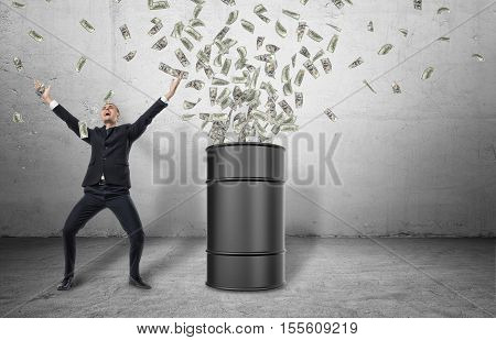 A barrel standing on the grey floor with loads of money bursting out of it and a happy businessman in a celebrating pose, on the grey background. Business and finance. Oil and gas industry. Successful people. Earning big money.