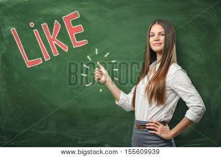 A young beautiful woman with thumbs up gesture standing near the big red word 'like' written on the green chalkboard. To get one's support and approval. Good idea. Social media and networking. luck and success in business.