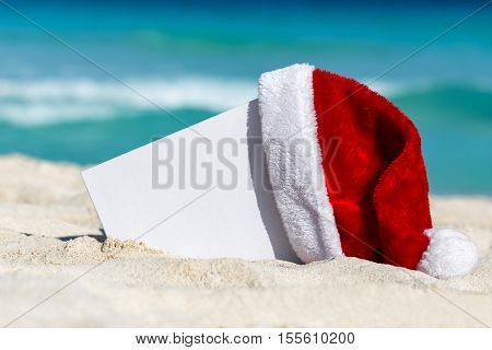 Santa Claus Hat And Blank Placard On Sandy Beach