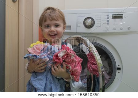 Happy cute little girl doing laundry in home interior. Mother's helper. 2 year old.