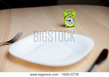 Alarm clockempty plate and utensils on a wooden background