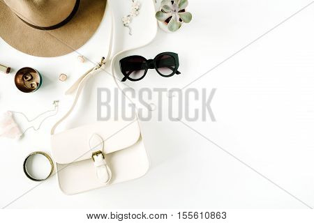 Flat lay trendy creative feminine accessories arrangement. Purse hat sunglasses female accessories. Top view
