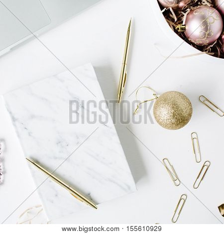 feminine workspace with laptop marble diary golden pen christmas decoration christmas balls tinsel bow on white background. flat lay top view