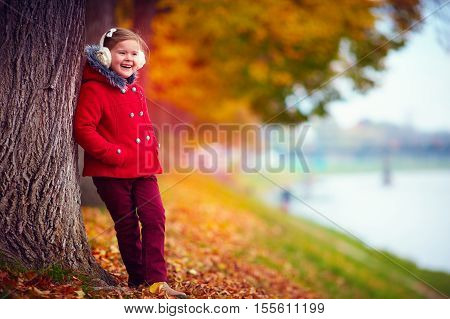 happy girl enjoys nature in autumn park