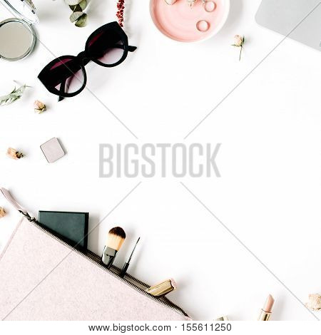 Flat lay top view office table desk frame. feminine desk workspace with laptop clutch cosmetics phone sunglasses lipstick rose buds on white background.