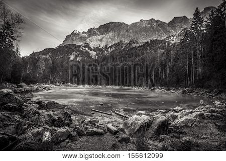 Black and white frozen lake - Frozen alpine lake surrounded with a rocky shore in the middle of the Bavarian Alps in the district of Garmisch-Partenkirchen Bavaria Germany