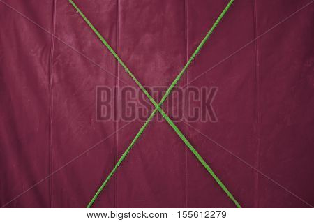 Texture red tarp with a green cross in the middle of the rope. Yellow background.