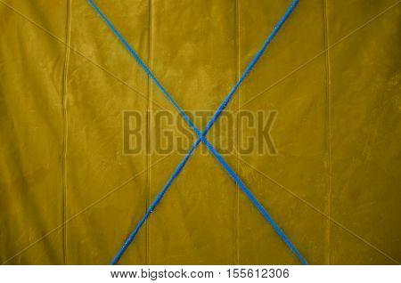 Texture yellow tarp with a blue cross in the middle of the rope. Yellow background.