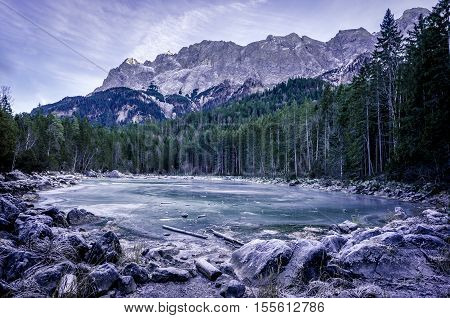 Frozen lake in the German Alps - Winter scenery with an alpine frozen lake surrounded by the German Alps near the municipality Grainau district Garmisch-Partenkirchen Bavaria Germany.