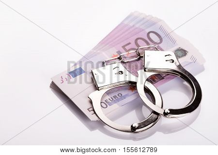 Pair Of Handcuffs Closeup On Euro Banknotes Stack