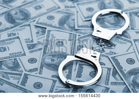 Pair Of Handcuffs Closeup On Dollar Banknotes Background