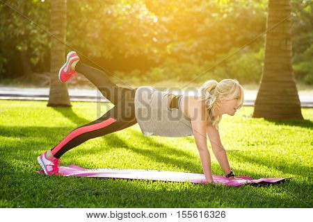 Young Beautiful Fitness Woman With Ponytail Doing Plank Position Outside  At The Park