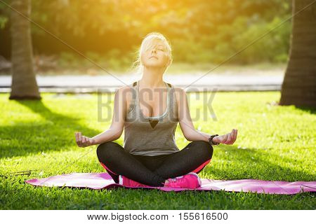 Woman Meditating On Green Grass At The Park Sitting In Lotus Position