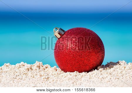 Red Fir Tree Decoration Ball On Sandy Beach