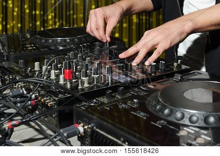 DJ at dance party mixes track on sound mixer, nightclub with striped yellow interior, nightlife entertainment industry