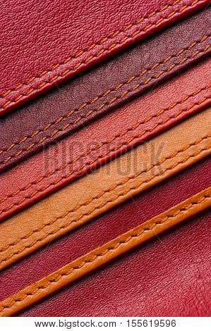 Leather samples with stitches, natural materials with seams of red, maroon, brown, orange colors and other warm shades, women bag detail, macro shot, selective focus