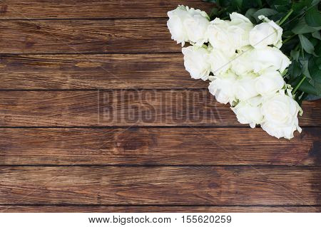 fifteen white roses on a wooden background with a place for an inscription