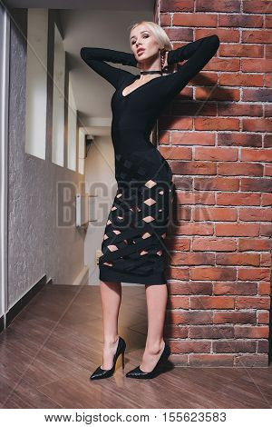 Woman standing near brick wall in black dress.