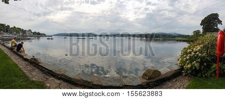 Ambleside England - September 13 2016: Panoramic view of Lake WIndermere with two people seated on the promenade