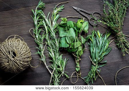 bundle of sage and thyme, mint, estragon on wooden background top view.